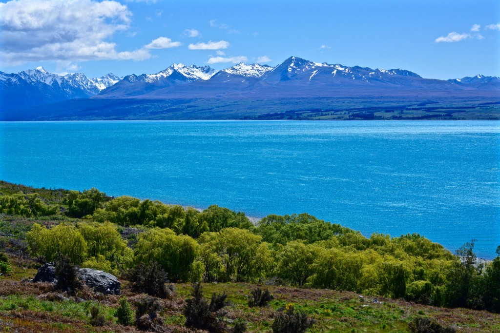 Crystal blue water in front of a mountain range